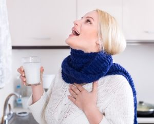 blonde-young-woman-having-pain-in-throat-and-doing-oral-rinsing-at-kitchen